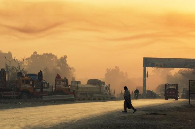 The rising sun lights smoke in the air as a man crosses the street near Forward Operating Base Fenty in the Nangarhar province of Afghanistan December 19, 2014. REUTERS/Lucas Jackson/Files