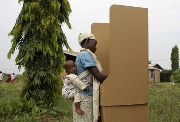 A woman carrying a child behind her marks her ballot in a booth at a polling station in Kinama neighbourhood during a parliamentary election near Bujumbura, on Monday. Photo: REUTERS