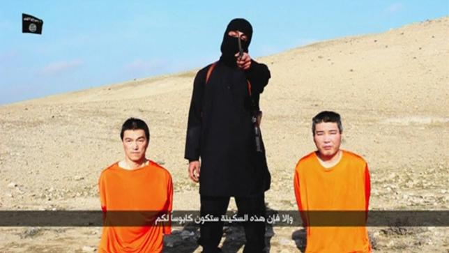 A masked person holding a knife speaks as he stands in between two kneeling men in this still image taken from an online video released by the militant Islamic State group on January 20, 2015. REUTERS/Social media website via Reuters TV