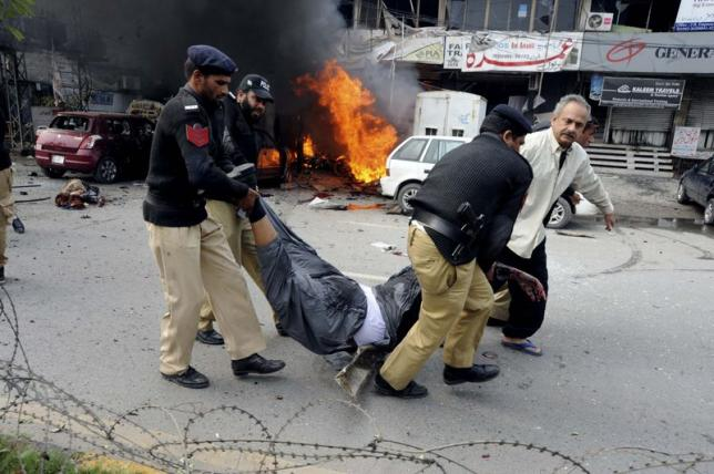 Policemen and residents move a dead body from the site of an explosion outside the police headquarters, in Lahore February 17, 2015. REUTERS/Imran Sheikh