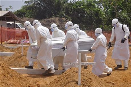 FILE - In this file photo taken on Wednesday, March 11, 2015, health workers carry a body of a person that they suspected died form the Ebola virus at a new graveyard on the outskirts of Monrovia, Liberia. AP