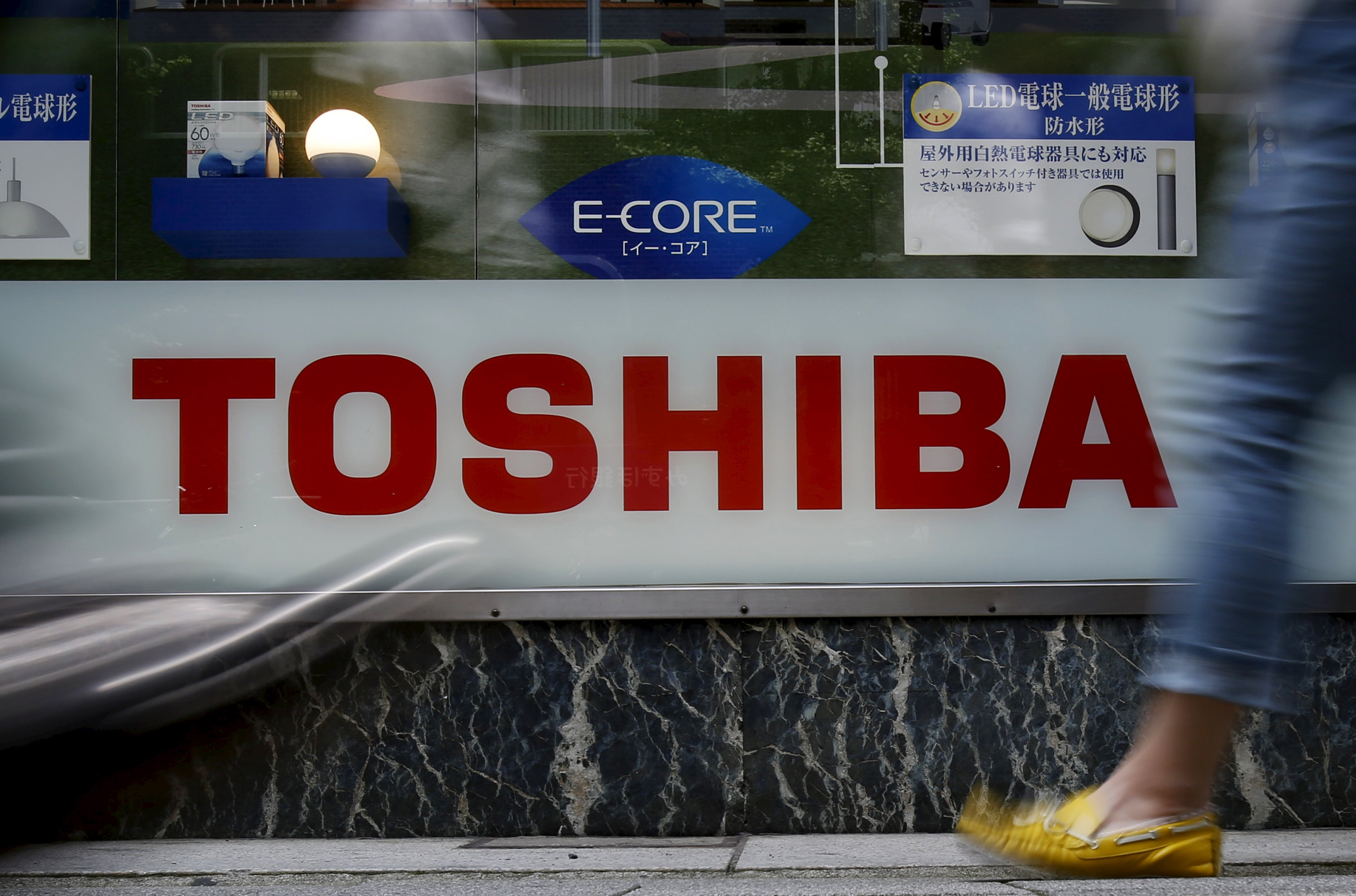 Pedestrians walk past a logo of Toshiba Corp outside an electronics retailer in Tokyo, Japan, June 25, 2015. Photo: Reuters
