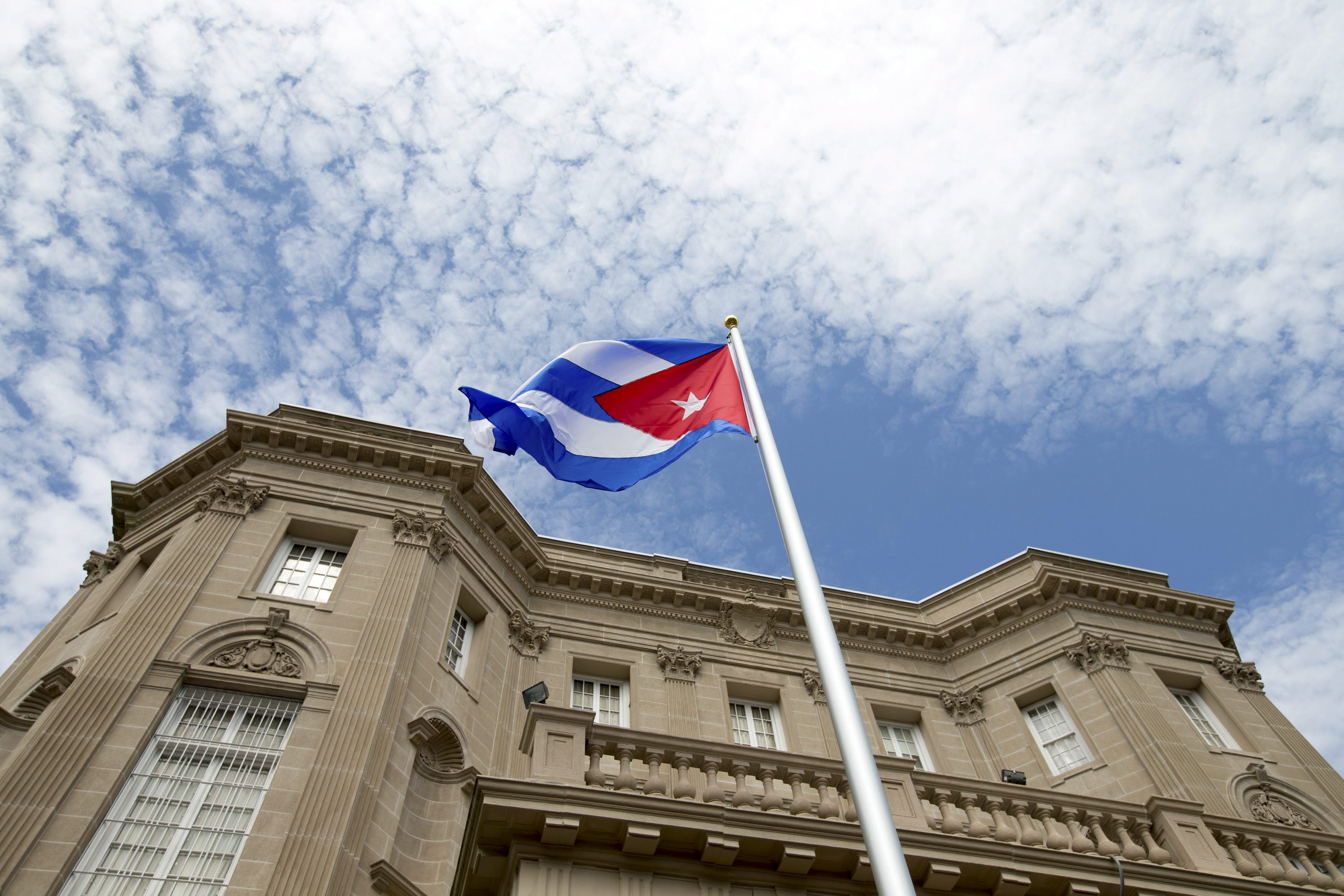The Cuban national flag is seen raised over their new embassy in Washington, July 20, 2015. The Cuban flag was raised over Havanau2019s embassy in Washington on Monday for the first time in 54 years as the United States and Cuba formally restored relations, opening a new chapter of engagement between the former Cold War foes.   REUTERS/Andrew Harnik/Pool      TPX IMAGES OF THE DAY