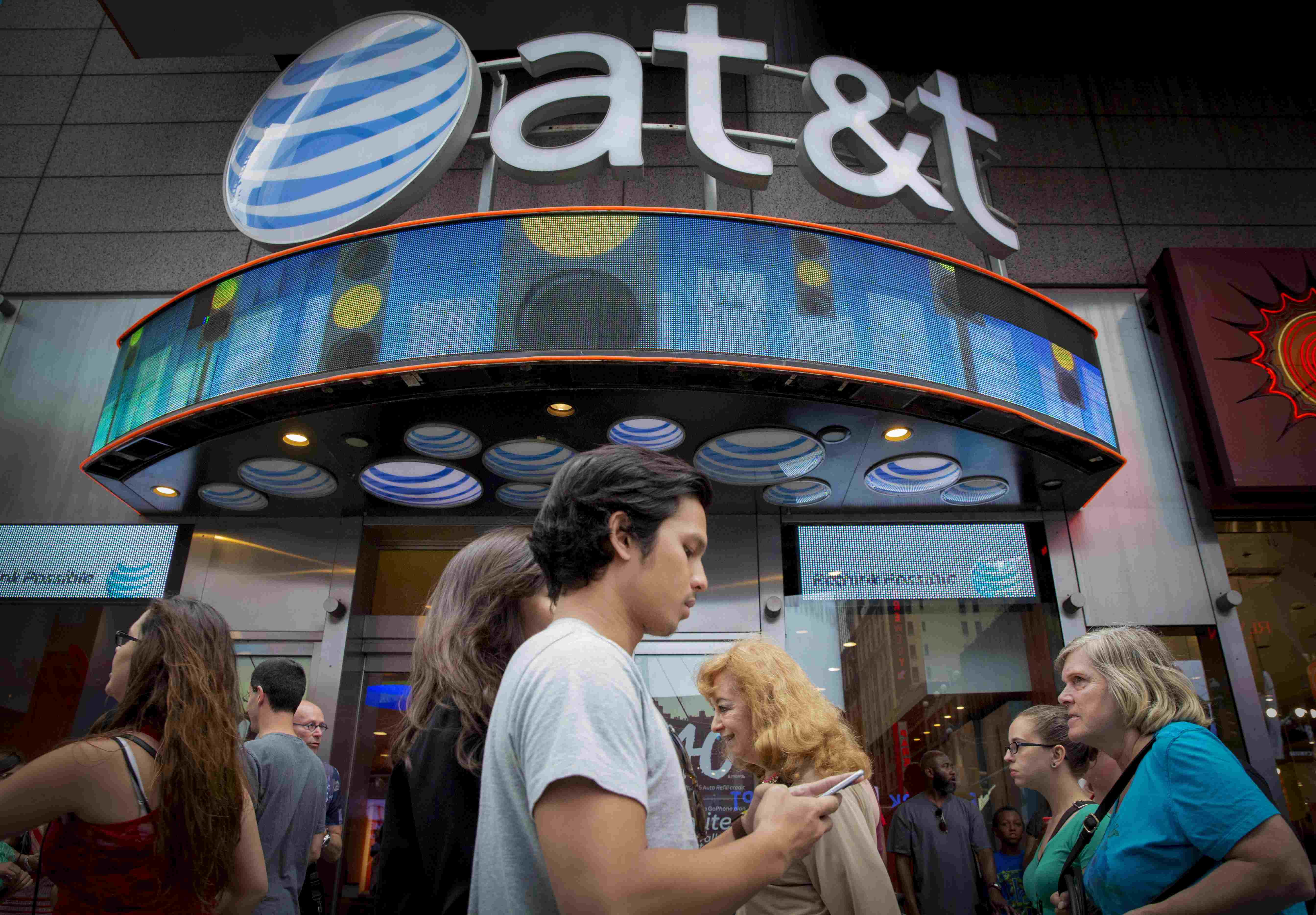 People walk past the AT&T store in New York's Times Square, in this June 17, 2015 file photo.  AT&T Inc reported a better-than-expected quarterly profit Thursday, as the second largest US Wireless carrier added post-paid customers. Photo: Reuters/ File