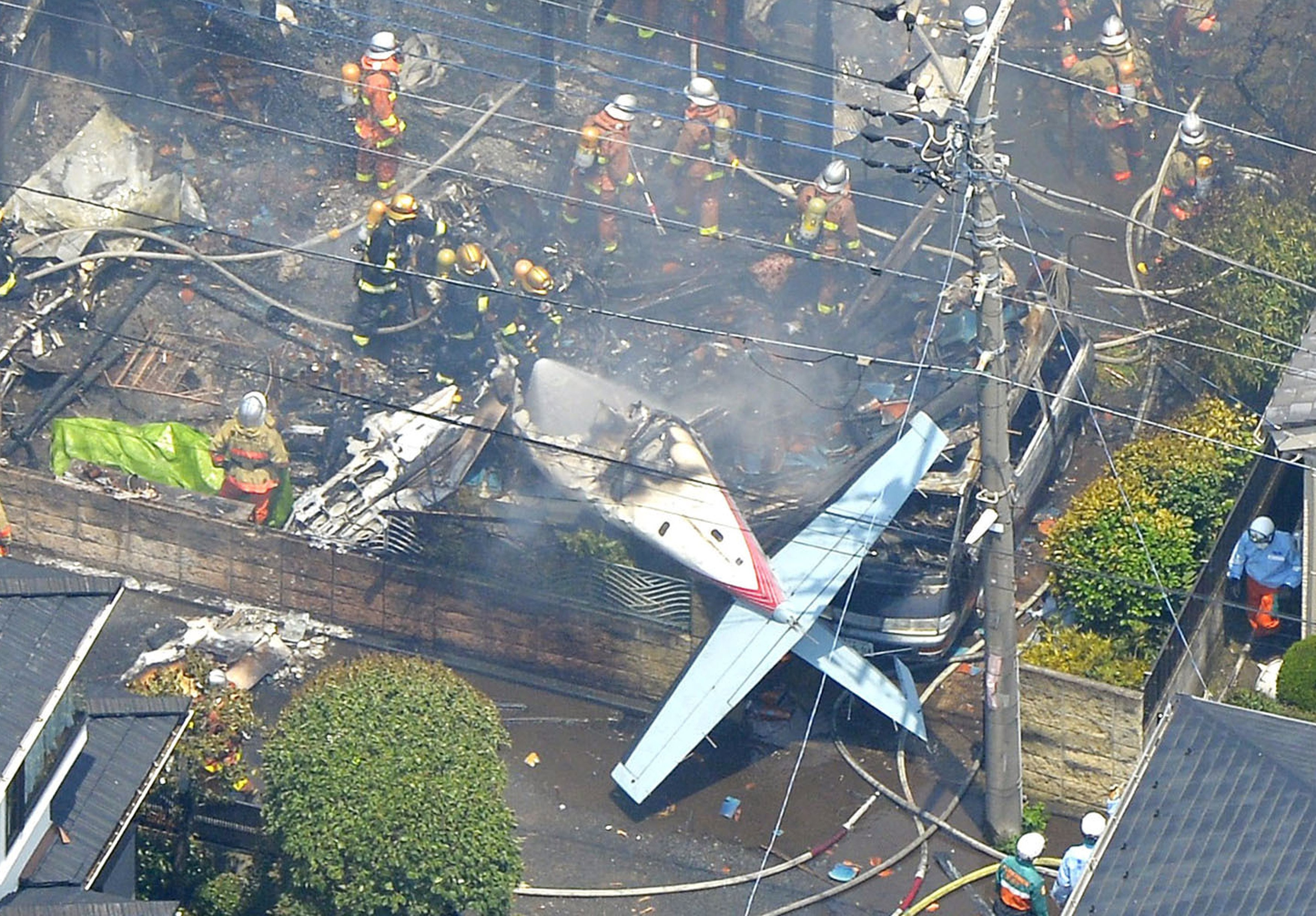 An aerial view shows debris of a crashed light plane (bottom centre) and burning houses are seen after the plane went down in a residential area and burst into flames, in Chofu, outskirt of Tokyo, in this photo taken by Kyodo July 26, 2015. A small airplane crashed into a residential area of the Japanese capital, Tokyo, on Sunday, setting fire to houses and cars and injuring at least two people, the Tokyo Fire Department said. Photo: Kyodo/ Reuters