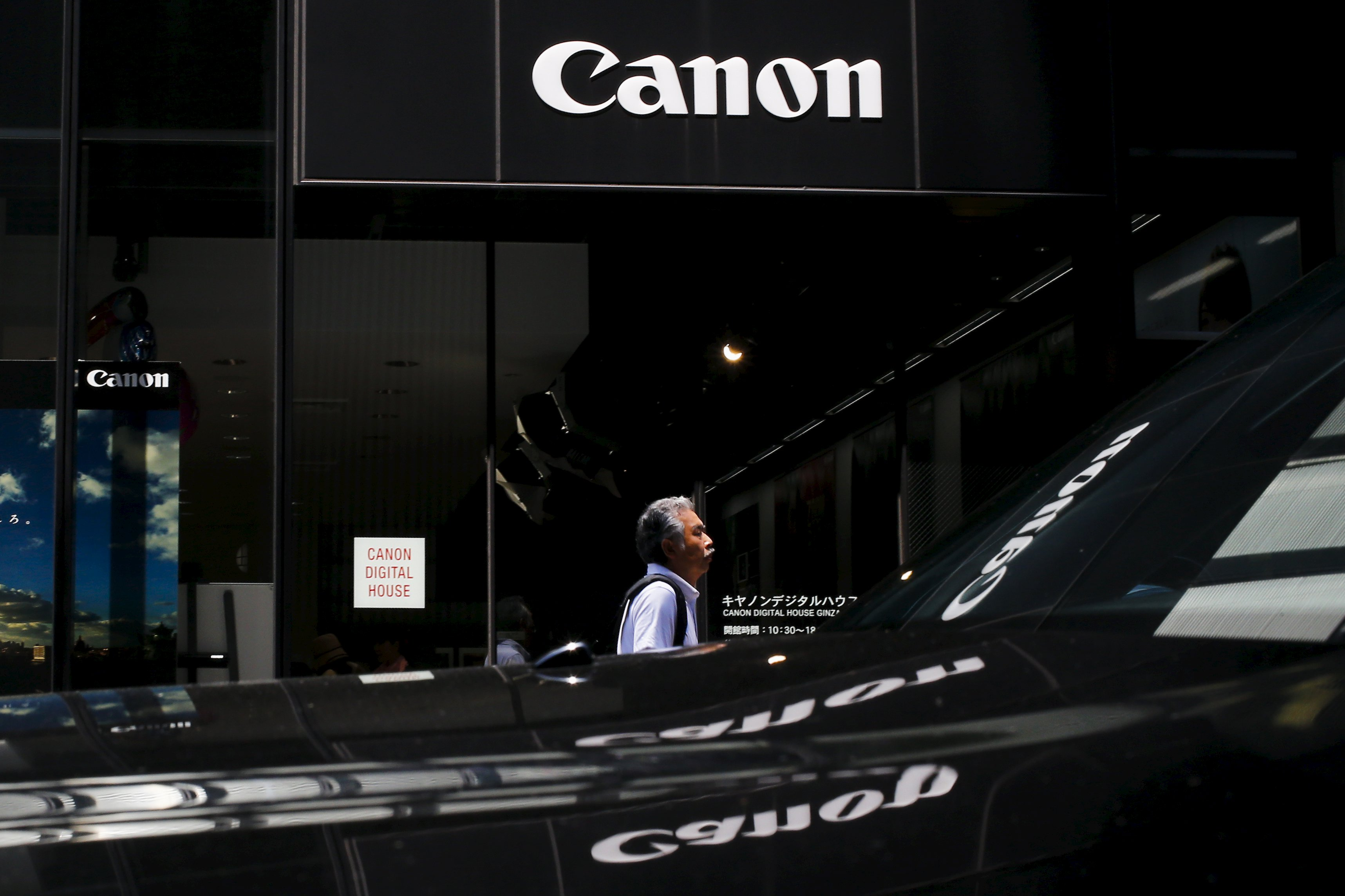 A man walks past a showroom of Japanese imaging and optical products manufacturer Canon in Tokyo July 27, 2015. Japan's Canon Inc on Monday lowered its earnings outlook for the full year and reported a 16 percent fall in second-quarter net profit, as fewer consumers bought new compact digital cameras. Photo: Reuters