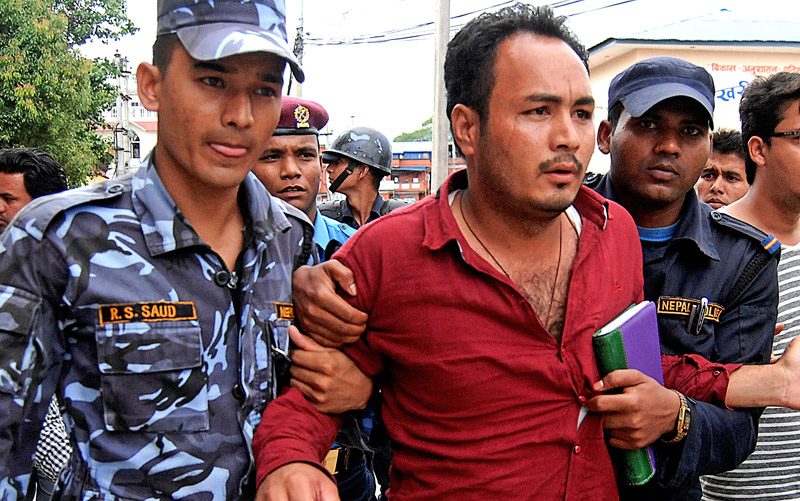A man being caught by policemen after protesting against the public hearing on the preliminary draft of the new constitution, at Kamaladi, in Kathmandu, on Tuesday. Photo: THT