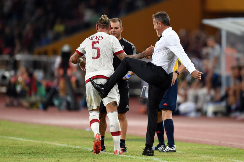 AC Milan Croatian head coach Sinisa Mihajlovic (R) kicks AC Milan's French defender Philippe Mexes (L) in celebration of scoring a goal during the International Champions Cup football match between AC Milan and  Inter Milan in Shenzhen on July 25, 2015.  Photo: AFP