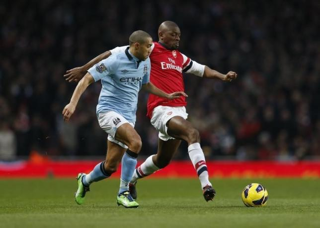 Arsenal's Abou Diaby (R) challenges Manchester City's Gael Clichy during their English Premier League soccer match at the Emirates Stadium in London January 13, 2013.     REUTERS/Eddie Keogh