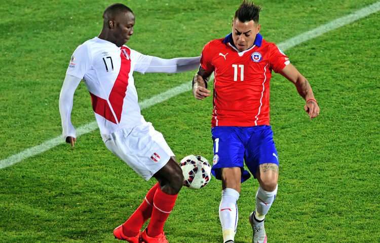 Peru's Luis Advincula (left) vies for the ball with Chile's Eduardo Vargas during their Copa America semi-final match in Santiago on Monday. Chile won 2-1. Photo: AFP