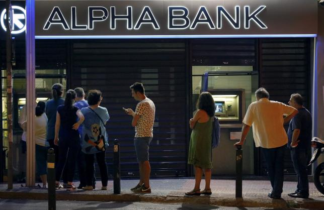 Greeks wait to withdraw the maximum amount for a day of sixty Euros from an ATM in Athens, Greece July 11, 2015. REUTERS/Yannis Behrakis