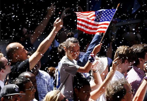 A fan holds an American flag as paper falls from buildings above during the ticker tape parade for the U.S. women's soccer team to celebrate their World Cup final win over Japan, in New York, July 10, 2015. REUTERS/Mike Segar