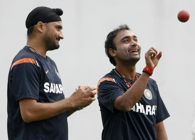 India's Amit Mishra (R) tosses the ball as teammate Harbhajan Singh prepares to bowl during a cricket practice session ahead of their first test cricket match against South Africa in Nagpur February 5, 2010. REUTERS/Arko Datta/Files
