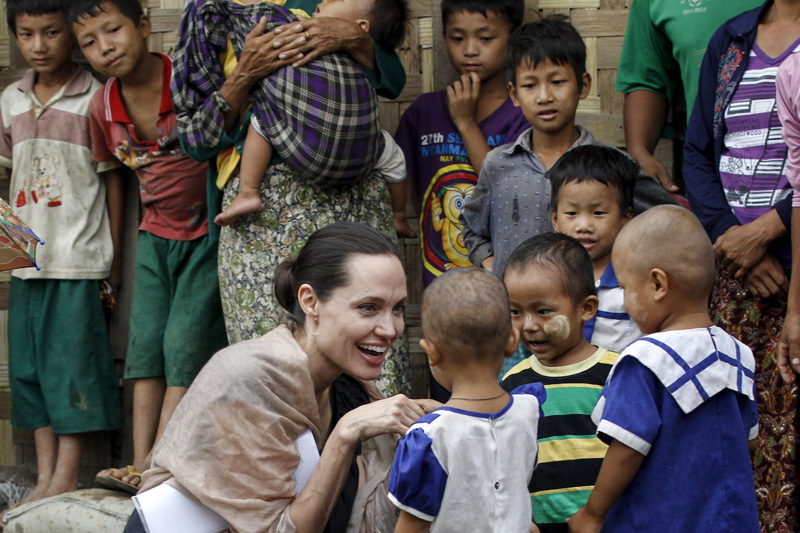 UNHCR special envoy Angelina Jolie Pitt shakes hand with Kachin ethnic refugee kid as she visits Eight Miles Palana IDP camp in Myitkyina capital city of Kachin state, Myanmar, on Thursday. Photo: Reuters
