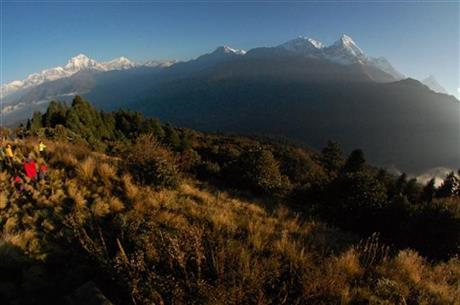 FILE - In this Oct. 24, 2014, file photo, trekkers watch the sun rise over the Annapurna Range, right, in central Nepal, as viewed from Poon Hill, above the village of Ghorepani. AP