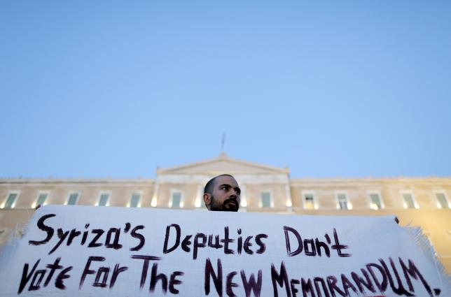 An anti-EU protester holds a banner in front of the parliament building during a demonstration of about five hundred people in Athens, Greece July 13, 2015. REUTERS/Christian Hartmann