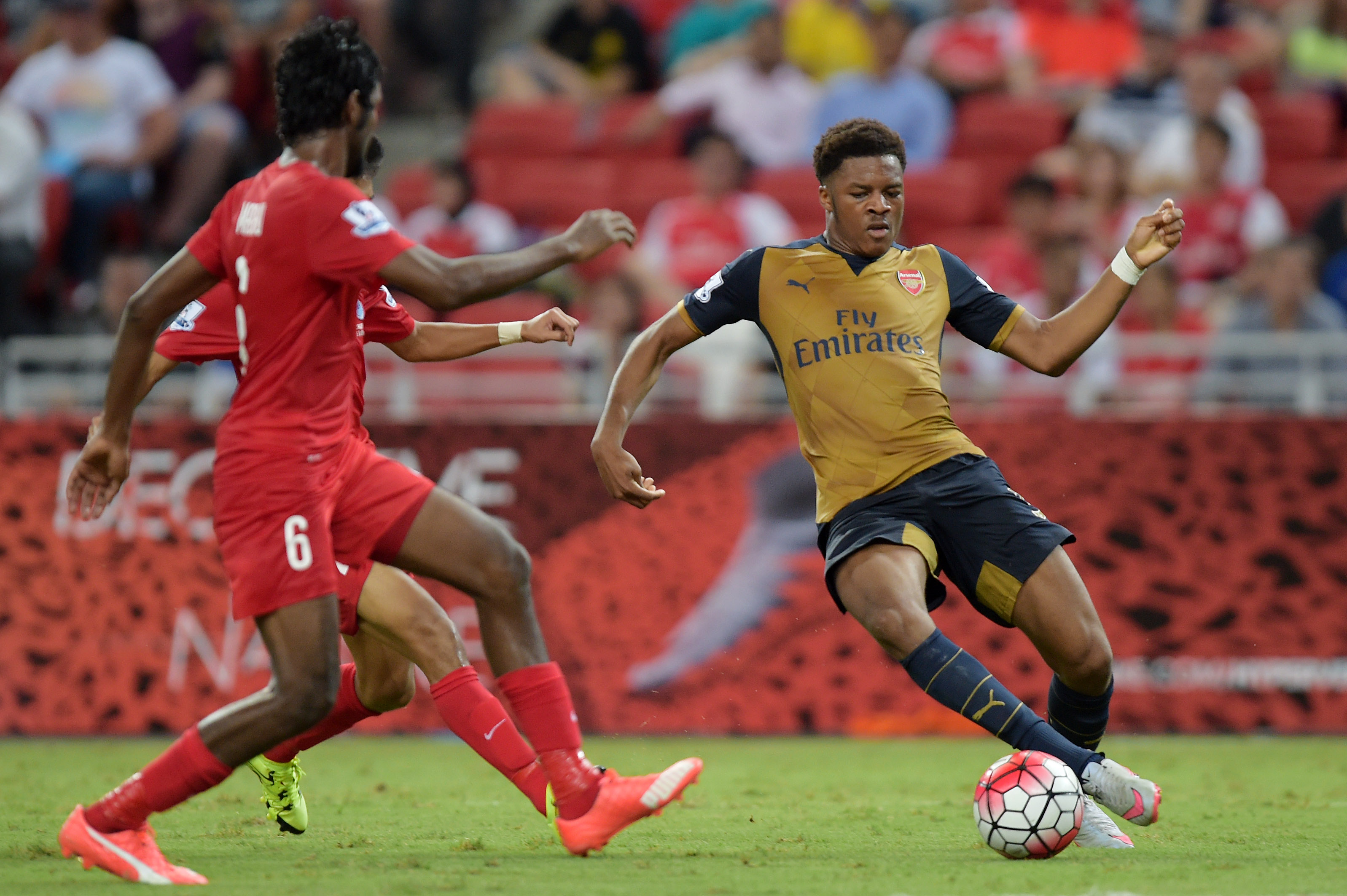 Arsenal's Chuba Akpom (right) dribbles past Singapore Selection Xl's Madhu Mohana (left) during their Barclays Asia Trophy football match at the Singapore National Stadium on Wednesday. Arsenal won the match 4-0. Photo: AP
