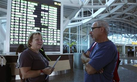Australian passengers check for their flight status at Bali's international airport, Indonesia Friday, July 10, 2015. A volcanic eruption on Indonesia's main island of Java has sparked chaos for holidaymakers as airports close and international airlines cancel flights to tourist hotspot Bali, stranding thousands. AP