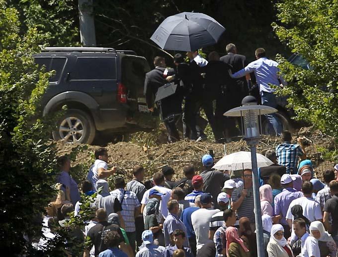 Bodyguards use umbrella to protect Serbia's Prime Minister Aleksandar Vucic during unrest at a ceremony marking the 20th anniversary of the Srebrenica massacre in Potocari, near Srebenica, Bosnia and Herzegovina July 11, 2015. Photo: Reuters