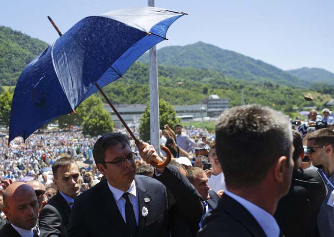A stone is thrown at Serbia's Prime Minister Aleksandar Vucic as bodyguards use umbrella to protect him during unrest at a ceremony marking the 20th anniversary of the Srebrenica massacre in Potocari, near Srebrenica, Bosnia and Herzegovina July 11, 2015. Photo: Reuters