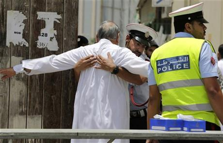 FILE- In this Friday, June 5, 2015 file photo, Bahraini community police officers search worshipers outside a Shiite Muslim mosque ahead of mid-day prayers in Manama. Bahraini authorities say two policemen have been killed and many injured in a bomb attack south of the capital. AP
