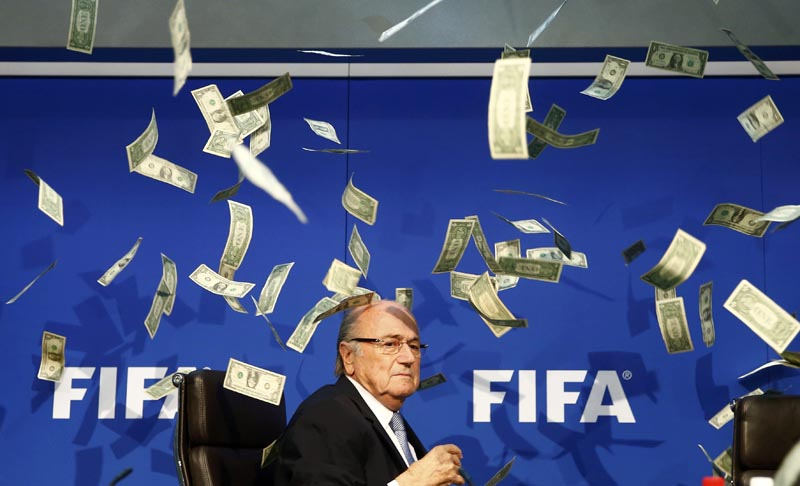 British comedian known as Lee Nelson (unseen) throws banknotes at FIFA President Sepp Blatter as he arrives for a news conference after the Extraordinary FIFA Executive Committee Meeting at the FIFA headquarters in Zurich, Switzerland July 20, 2015. Photo: Reuters