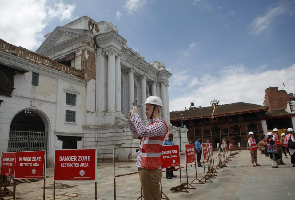 A foreign delegate photographs damaged buildings at the Basantapur Durbar Square heritage site in Kathmandu, Nepal, Wednesday, June 24, 2015. Photo: AP