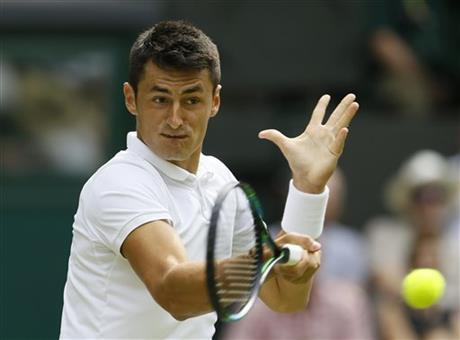 Bernard Tomic of Australia returns a ball to Novak Djokovic of Serbia during their singles match at the All England Lawn Tennis Championships in Wimbledon, London, Friday July 3, 2015. AP