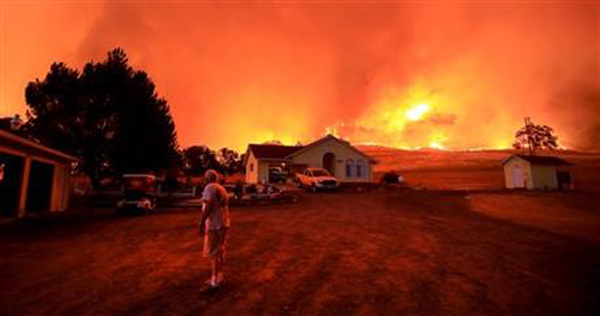 A wall of flames lurches over a ridge as a resident of Morgan Valley Road near Lower Lake, Calif., prepares to evacuate because of the Rock Fire, Wednesday evening July 29, 2015. Photo:AP