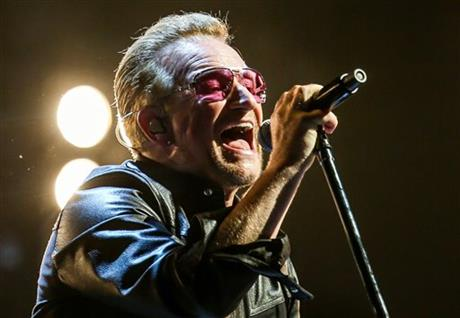 FILE - In this May 26, 2015, file photo, Bono of U2 performs at the Innocence + Experience Tour at The Forum in Inglewood, Calif. The special guests at U2u2019s concert Thursday night, July 30, 2015 in New York, included Paul Simon, Lou Reedu2019s widow and the woman who called 911 when Bono fell off his bike in New York City last year. AP