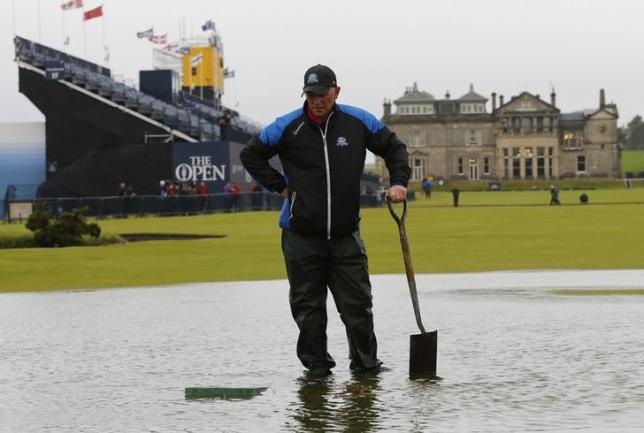 A member of the groundstaff stands in a puddle on the first fairway after torrential rain caused play to be suspendedn during the second round of the British Open golf championship on the Old Course in St. Andrews, Scotland, July 17, 2015.   REUTERS/Paul Childs