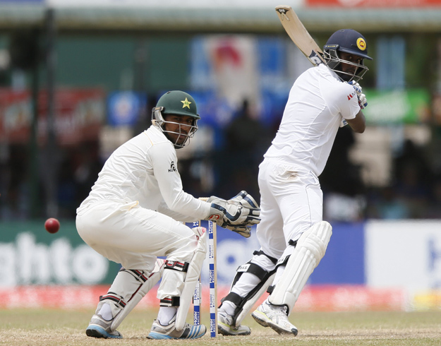 Sri Lanka's Angelo Mathews (R) hits a four next to Pakistan's wicketkeeper Sarfraz Ahmed during the final day of their second test cricket match in Colombo June 29, 2015. REUTERS/Dinuka Liyanawatte