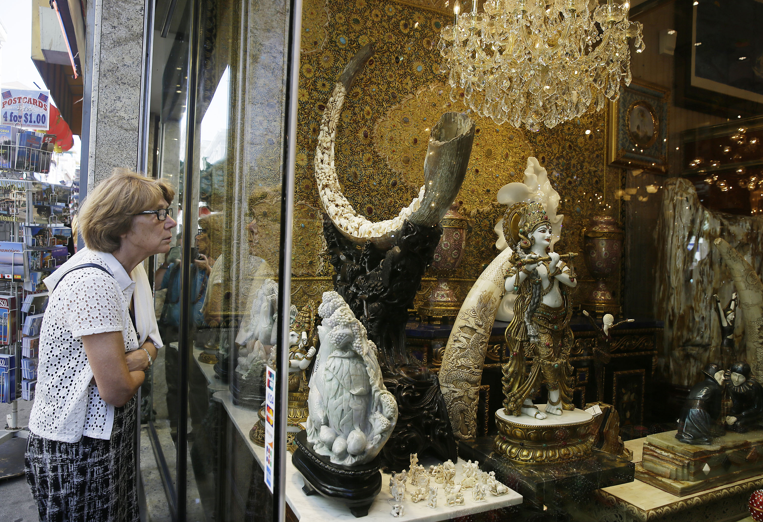 In this Monday, July 27, 2015 photo, Heike Dietrich, of Germany, looks at a mammoth ivory tusk for sale in the window of a Chinatown shop in San Francisco. Merchants of carved ivory tusks and trinkets in San Francisco's Chinatown wonder what impact President Obama's sweeping new order restricting ivory sales will have in California, the country's No. 2 market for elephant ivory. Lawmakers in New York recently closed most loopholes allowing ivory sales, but California lawmakers this summer rejected similar measures. Photo: AP