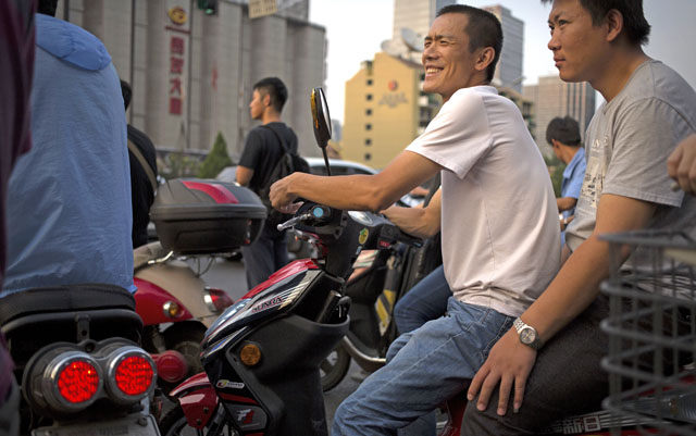 Men sitting on an electric scooter as they wait for a traffic light to change during rush hour in nBeijing, on Thursday. Although car ownership rates have soared in China's capital, many residents still rely on scooters and bicycles to get around. Photo: AP