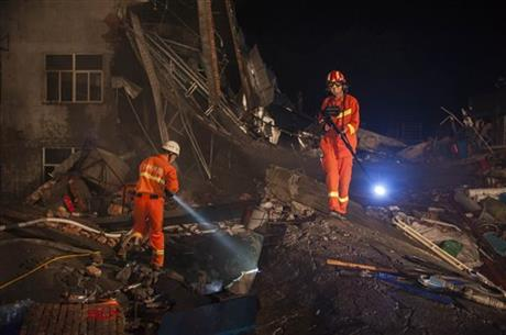 Rescuers shine flashlights across the rubble of a factory building in Wenling city in eastern China's Zhejiang province Saturday, July 4, 2015. Officials say the shoe factory collapsed during a weekend shift. The cause of the accident is still under investigation.AP