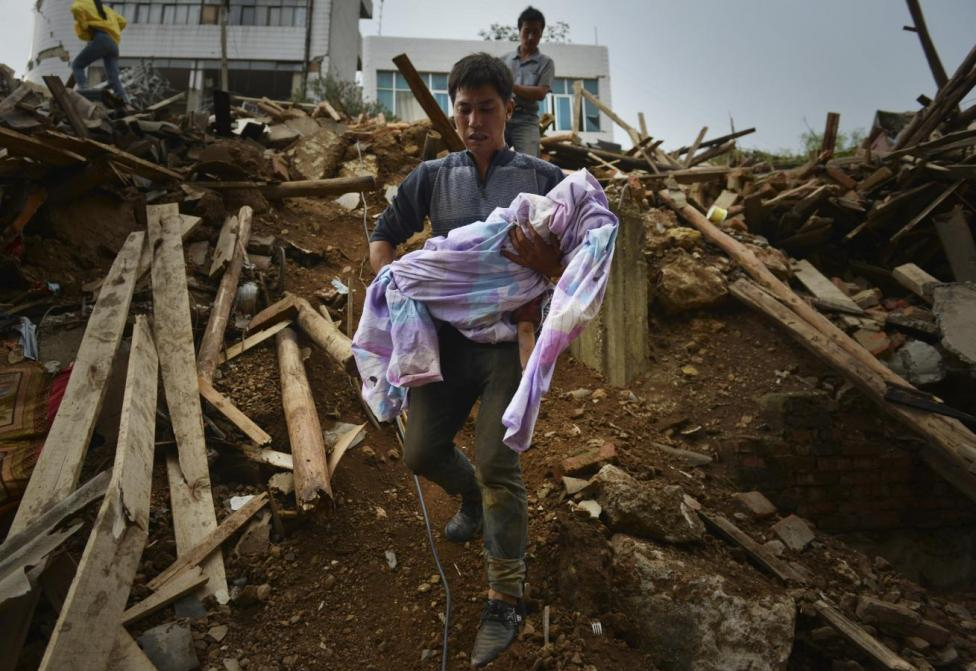 Mao Changxue carries the body of his son after it was dug out from the debris of their home, which collapsed when a magnitude 6.3 earthquake hit Longtoushan town, Ludian county of Zhaotong, Yunnan province, August 4, 2014. nREUTERS/Stringer