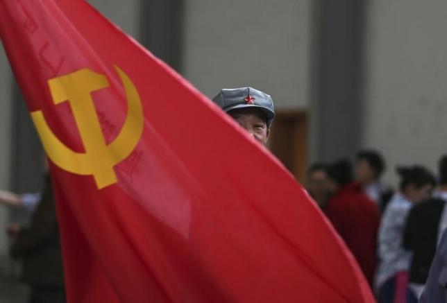 A participant waves a Chinese Communist Party flag in Kunming, Yunnan province January 31, 2015. REUTERS/Stringer/Files