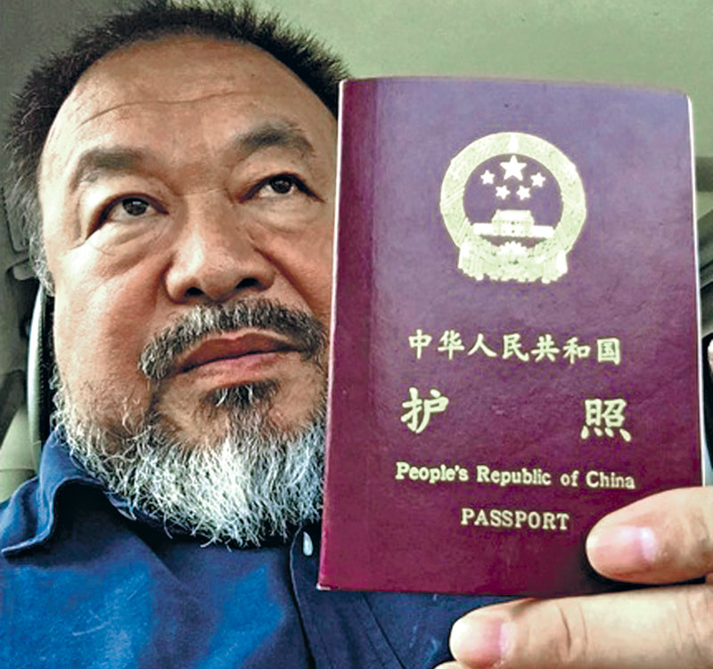 Chinese dissident artist Ai Weiwei posing with his npassport in Beijing in this handout picture provided to Reuters on Wednesday. Weiwei said that authorities in Beijing returned his passport after four years. Photo: Reuters