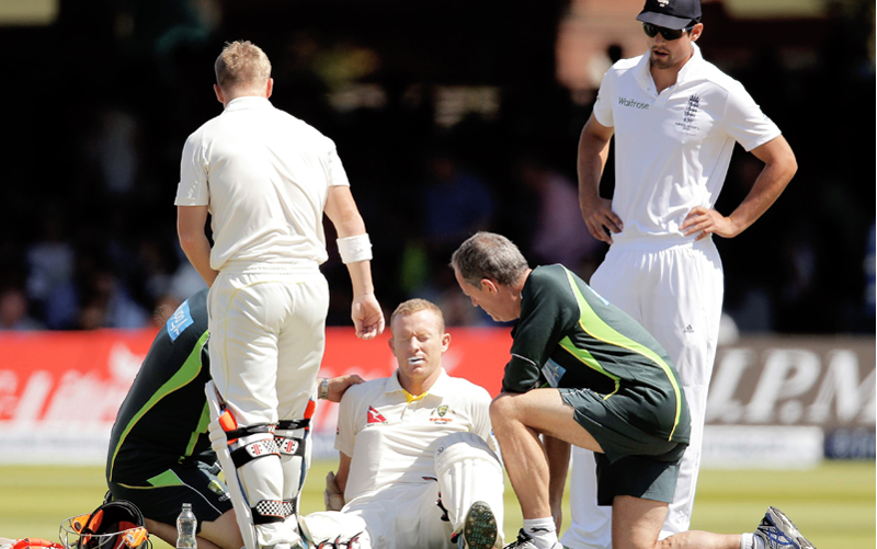 Australia's Chris Rogers (centre) gets treatment on the pitch on the fourth day of the second Ashes Test match against England at Lord's in London on Sunday. Photo: Reuters