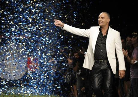 FILE - In this Oct. 15, 2008 file photo, designer Christian Audigier gestures to the crowd after his Christian Audigier Presents American Lord show during Mercedes-Benz fashion week in Culver City, Calif. AP