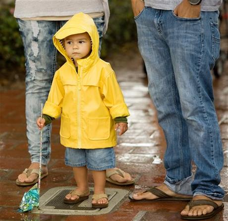Ezekiel Ekinaka, 1, with his parents Aaron and Juliet, wears a raincoat as he experiences rain for the second time in his life, at the San Clemente, Calif. Ocean Festival before the public was urged to evacuate due to lightning on Saturday, July 18, 2015. AP