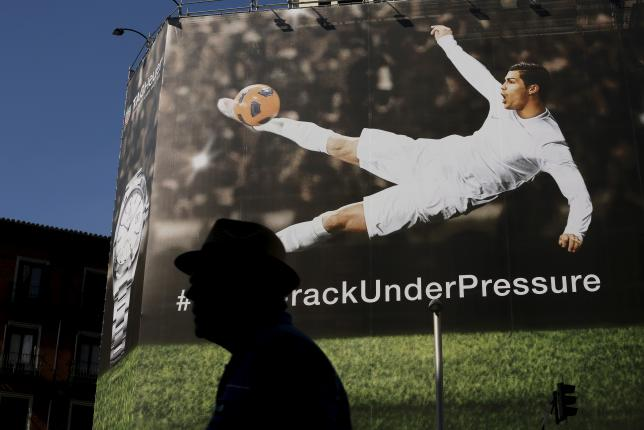 A man walks past a billboard displaying an image of Real Madrid's soccer player Cristiano Ronaldo kicking a ball as part of an advertising campaign in central Madrid, Spain, June 25, 2015. Photo: Reuters