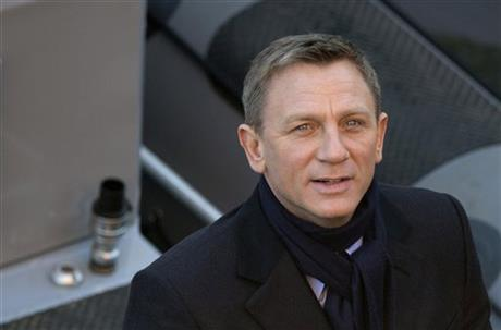 In this Tuesday, Dec. 16, 2014 file photo, actor Daniel Craig smiles for photographers as he films a scene for the new James Bond film, Spectre, in London. Stars including Daniel Craig and Judi Dench are urging the British government and signed the Wednesday July 15, 2015 letter to Prime Minister David Cameron to protect the BBC, as the publicly funded broadcaster faces budget cuts and political pressure for its ambitions to be curbed. AP
