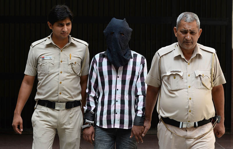 Indian police officers escort Ravinder Kumar, who is accused of murdering and sexual assaulting a six-year-old girl, at a police station in New Delhi on July 20, 2015.  Photo: AFP