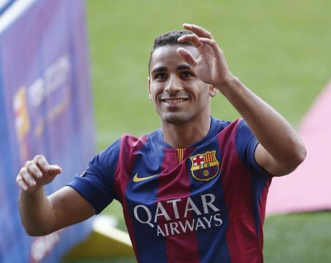 Barcelona's soccer player Douglas waves to supporters during his presentation at Nou Camp stadium in Barcelona August 29, 2014. REUTERS/Gustau Nacarino/Files
