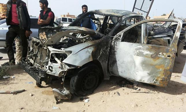 People stand at the scene of a car bomb explosion in the eastern city of Tobruk, near the Egyptian border November 12, 2014.  REUTERS/Stringer