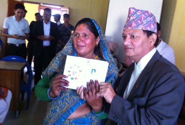 Regional Administrator Sarad Raj Bista handing over a farmeru0092s ID card to a woman at a programme organised in District Agriculture Office, Dadeldhura, on Wednesday. Photo: THT