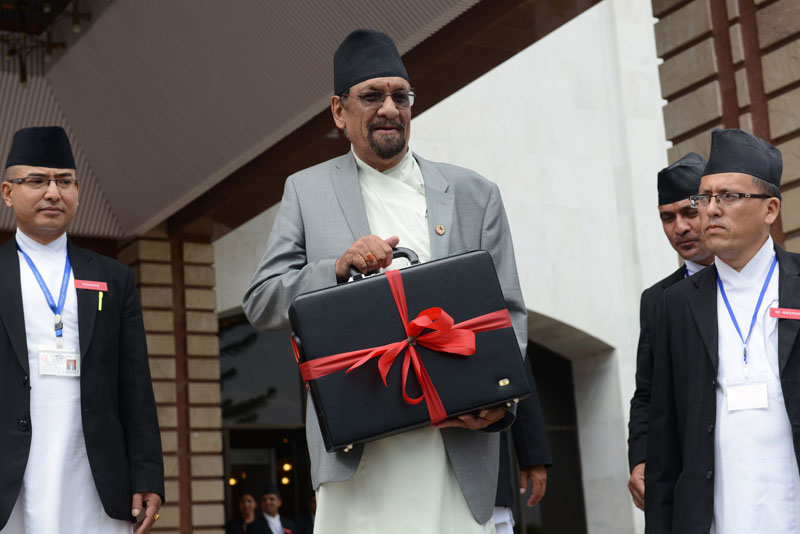 Nepal's Finance Minister Ram Sharan Mahat (C) carries a briefcase with the new government's budget for fiscal year 2015/2016 in Kathmandu on July 14, 2015.  Photo: AFP