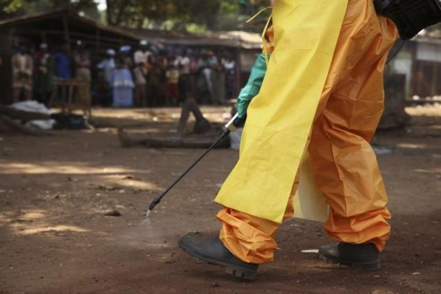 A member of the French Red Cross disinfects the area around a motionless person suspected of carrying the Ebola virus as a crowd gathers in Forecariah January 30, 2015.  Photo: Reuters