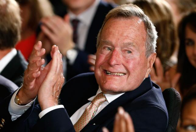 Former President George H. W. Bush applauds during an event to honor the winner of the 5,000th Daily Point of Light Award at the White House in Washington in this file photo from July 15, 2013. REUTERS/Kevin Lamarque/Files